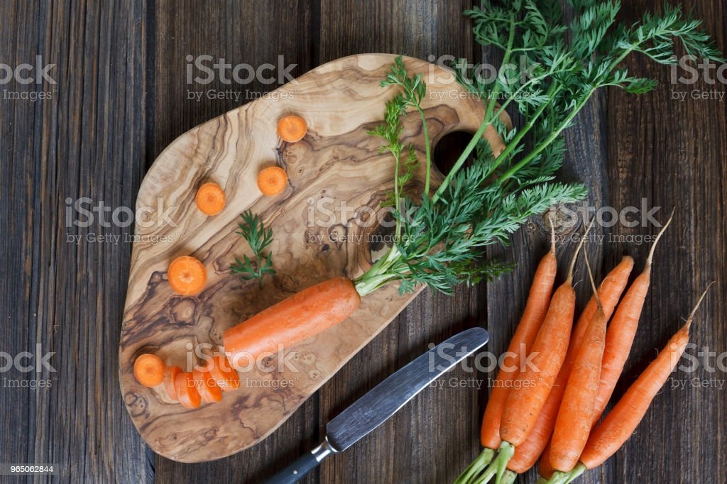 Close-up of fresh raw carrot on wooden board with knife. Top view on rustic wooden background royalty-free stock photo