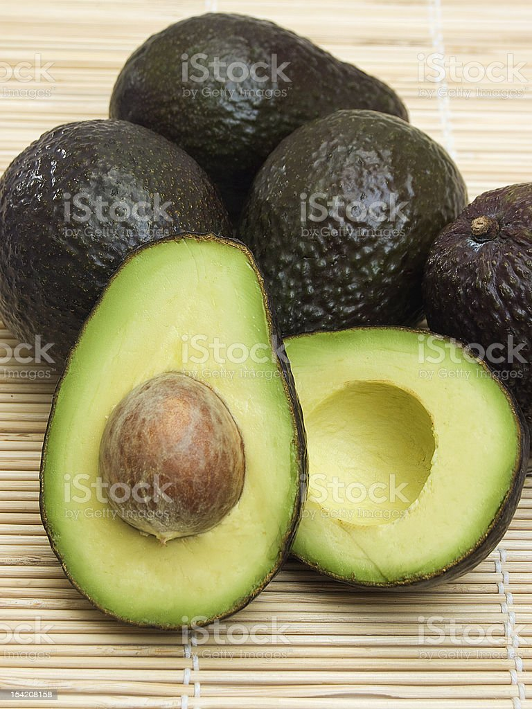 Close-up of fresh ripe avocado fruits on bamboo sheet royalty-free stock photo