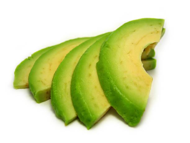 Close-up of fresh ripe avocado slices on white background stock photo
