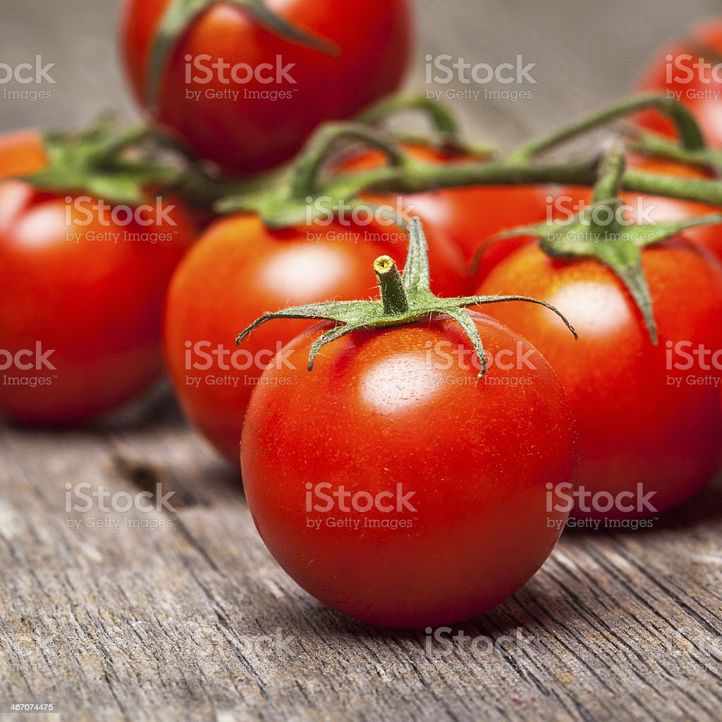 Close-up of fresh, ripe cherry tomatoes on wood stock photo
