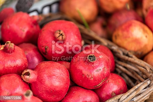 Closeup of fresh ripe, pink or red pomegranate round fruit, skin, whole in street farmer's market display bakset in Italy during summer, colorful vibrant
