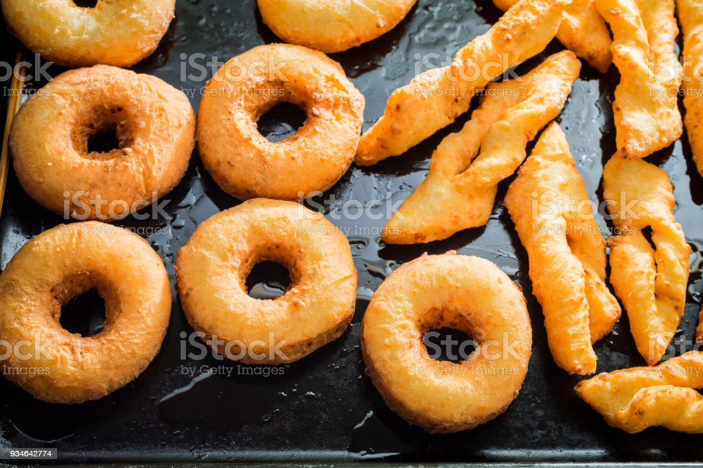 Closeup of freshly baked golden donuts on black tray stock photo
