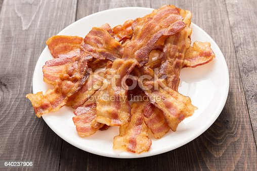 istock Closeup of fried bacon strips on white plate 640237906