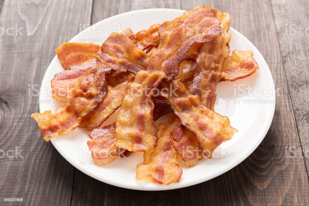 Closeup of fried bacon strips on white plate stock photo