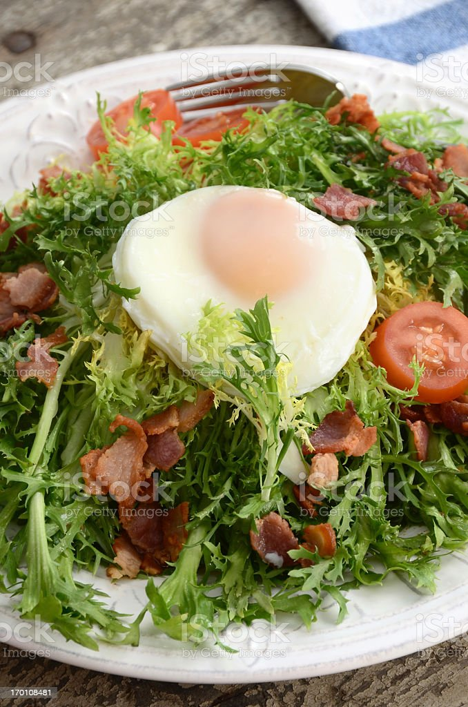 Close-up of Frisee salad with lardons and poached egg stock photo