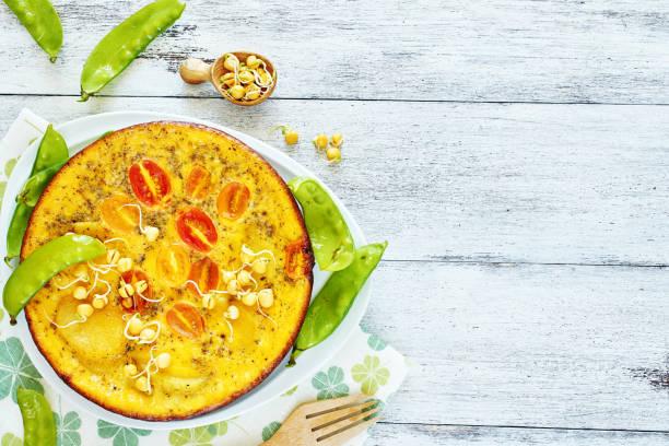 nahaufnahme der frittata (omelette) mit kartoffeln, tomaten und junge erbsen auf einem weißen tisch mit textfreiraum. - kartoffel frittata stock-fotos und bilder