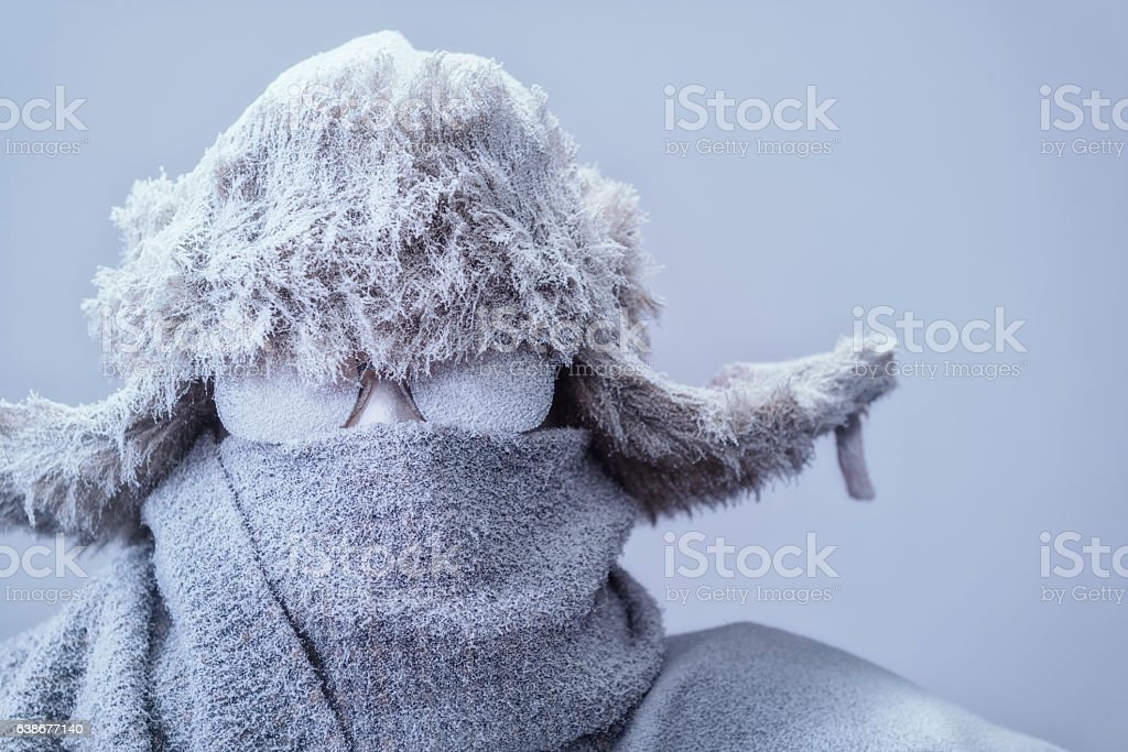 Close-up of frozen man in parka, hat and scarf stock photo