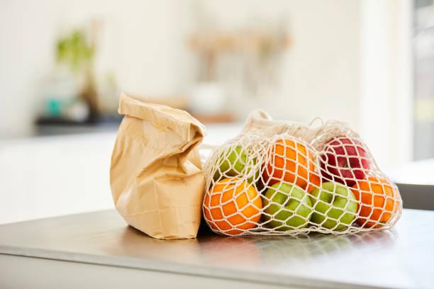 Nahaufnahme von Früchten und Papiertüten auf Kücheninsel – Foto