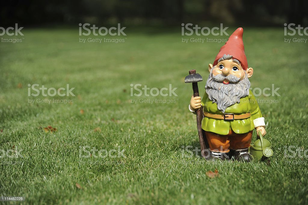 Close-up of garden gnome holding pickax and watering can stock photo