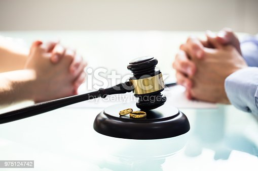 istock Close-up Of Gavel And Wedding Rings 975124742