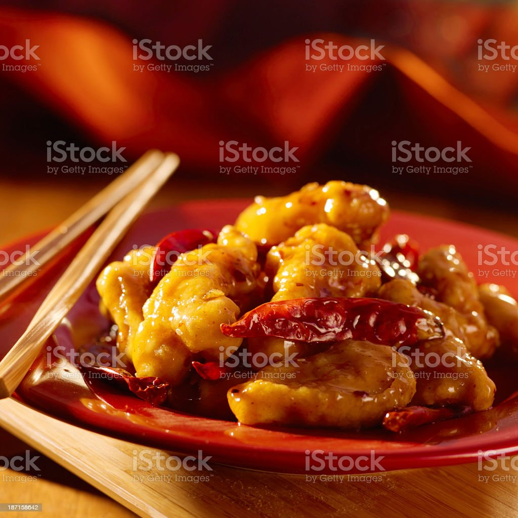 Close-up of General Tso chicken dish on red with chopsticks royalty-free stock photo