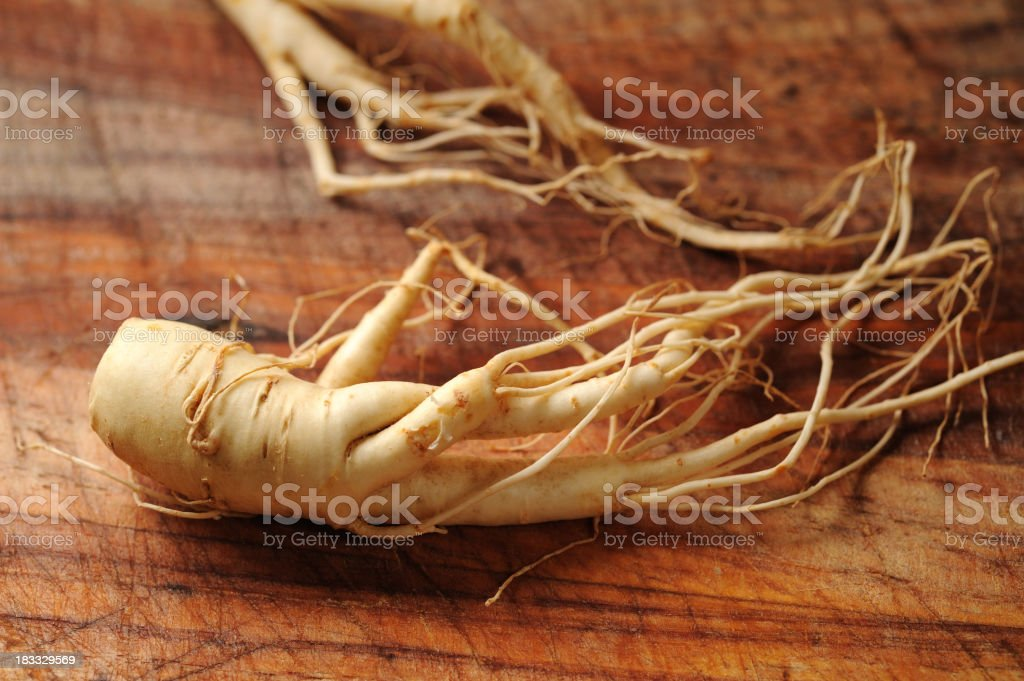 Close-up of ginseng roots on a wooden surface stock photo