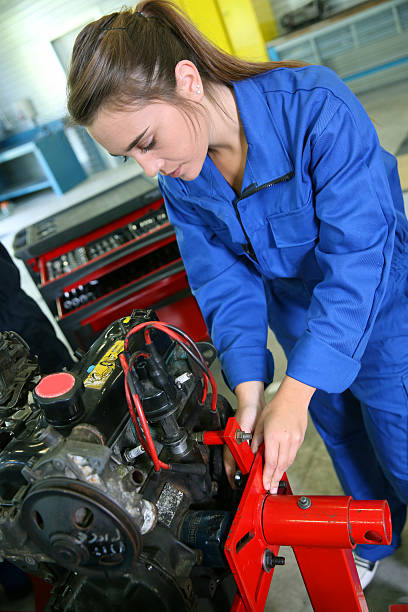 Closeup of girl in blue dungarees working at garage stock photo