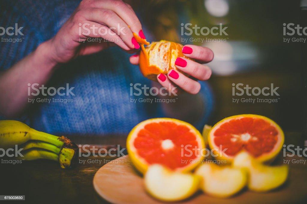 Close-up of girl peeling orange and grapefruit to make smoothie stock photo