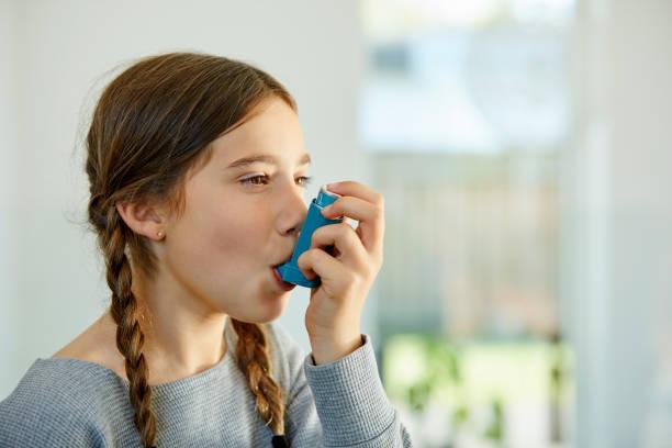 närbild av flicka som använder astma inhalator hemma - astmatisk bildbanksfoton och bilder