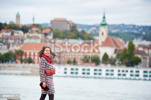 istock Close-up of girl walks along the embankment of Budapest with blurred view of Buda side of Budapest with the Buda Castle, St. Matthias and Fisherman's Bastion. Her hair is blown by the wind. 899858270