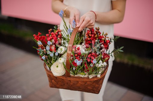 Close-up of blond girl with ponytail with brown basket of red and blue flowers