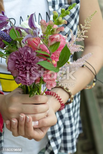 Closeup of girl's hands holding a bouquet of wildflowers, selective focus.