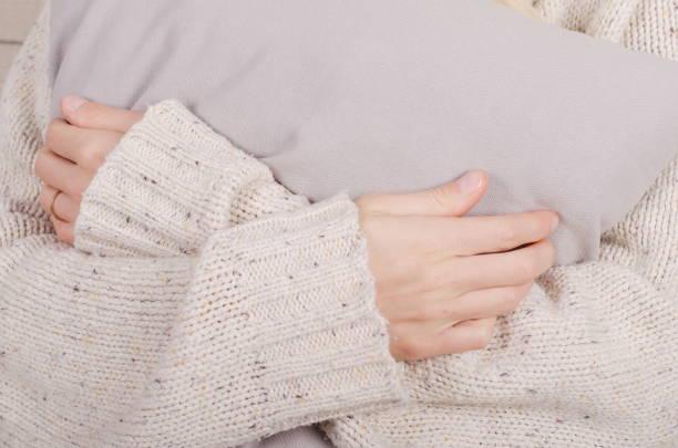 Gros plan des mains de la jeune fille dans un chandail de laine beige occasionnels étreignant un oreiller gris - Photo