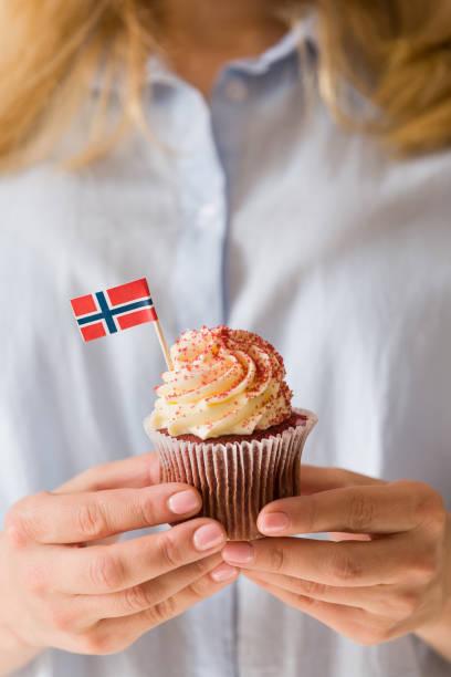 nahaufnahme der hände des mädchens mit delicios cupcake mit sahne mit norwegischer flagge dekoriert. feier 17. mai - norwegen fahne stock-fotos und bilder