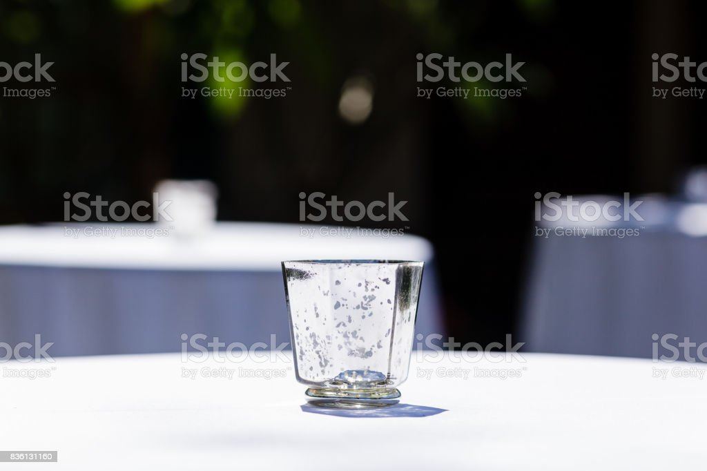 Close-up of glass tealight holder on white table with blurred background stock photo