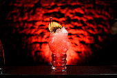 Close-up of glass with bright red cocktail with ice decorated with slices of citrus and glass tube for drinking.