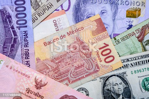 A close-up of global currencies showing dollar bills from USA, Philippines, Sweden, Euro, Indonesia, Australia, Vietnam, Thailand, New Zealand, Malaysia, Peru and Mexico.