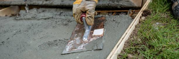 nahaufnahme der behandschuhten hand glätten betonoberfläche - diy beton stock-fotos und bilder