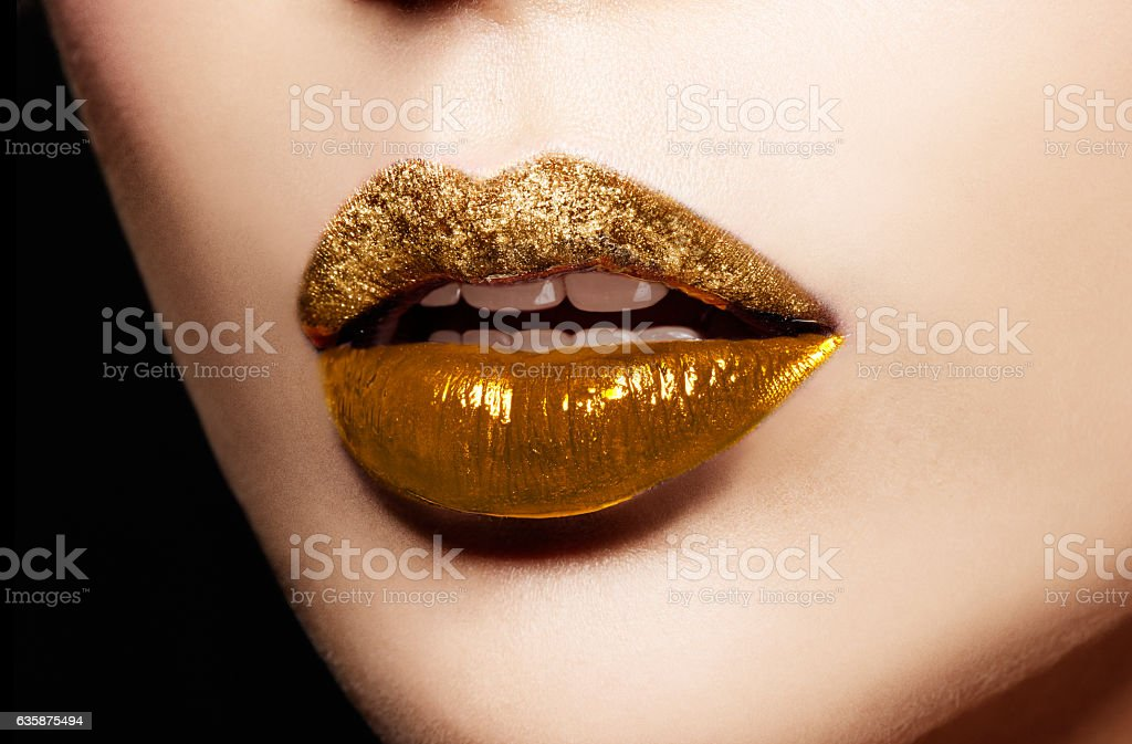 Closeup of gold artistic lips. Makeup cosmetic image. stock photo