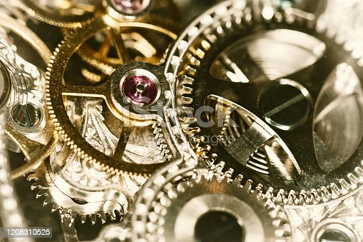 A look inside the workings of a wristwatch with multiple intricate cogs and gears, all interlinked.