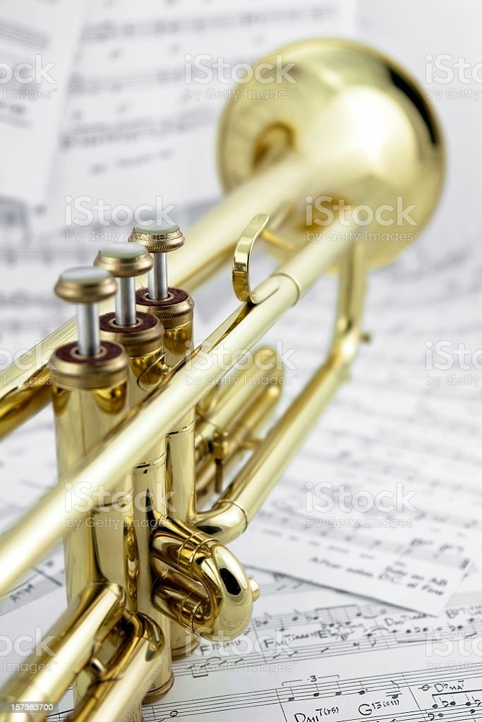 Close-up of golden trumpet lying on music notes, back view royalty-free stock photo