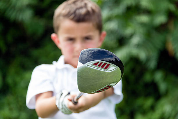 Close-up of golf driver club head held by boy golfer stock photo