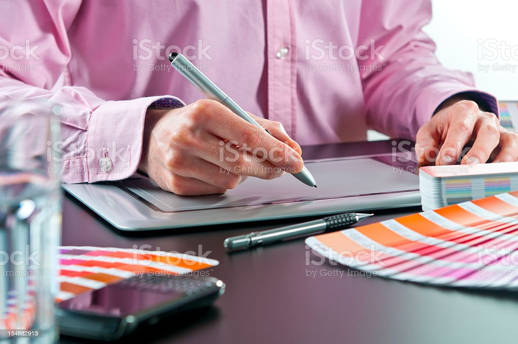 Close-up of graphic designer working on digital tablet, colour swatches stock photo