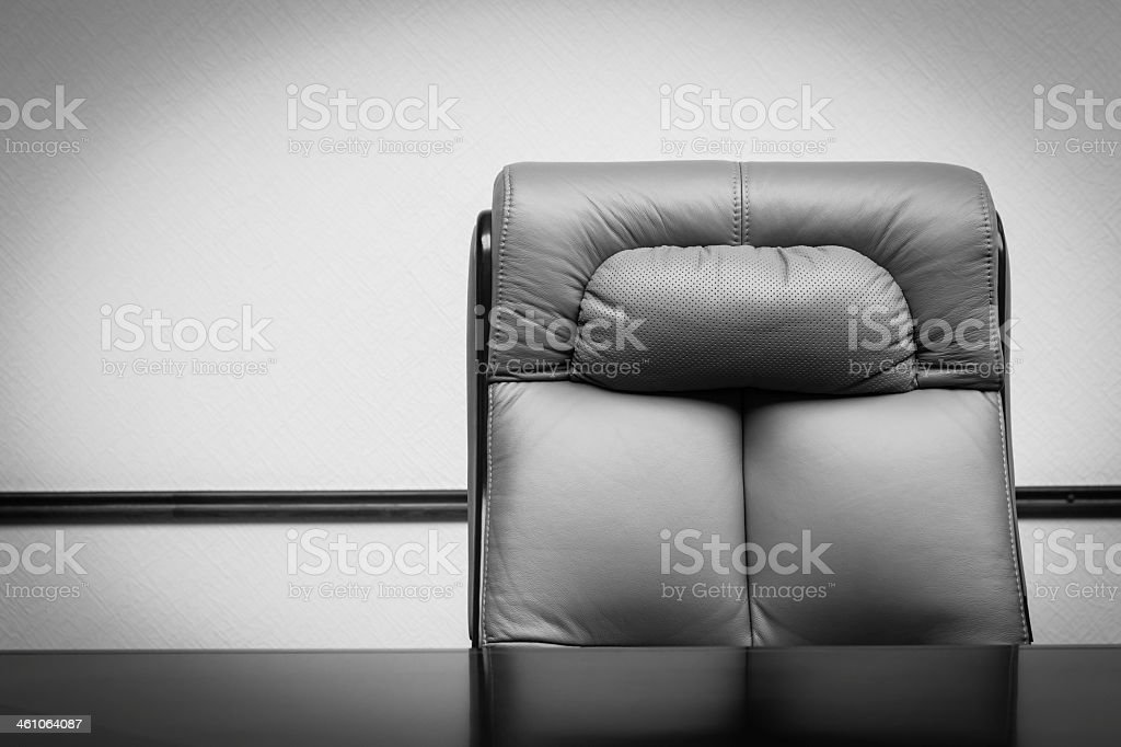 Close-up of gray leather chair and wooden desk stock photo