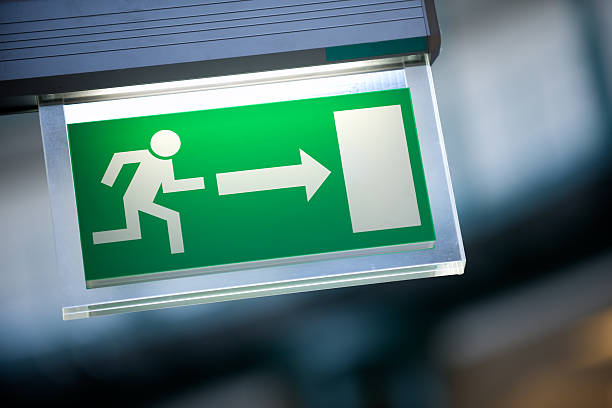 close-up of green emergency exit light sign - leaving stock photos and pictures