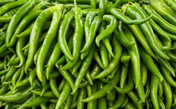 close-up of green hot chili peppers - green chilli pepper stock photos and pictures