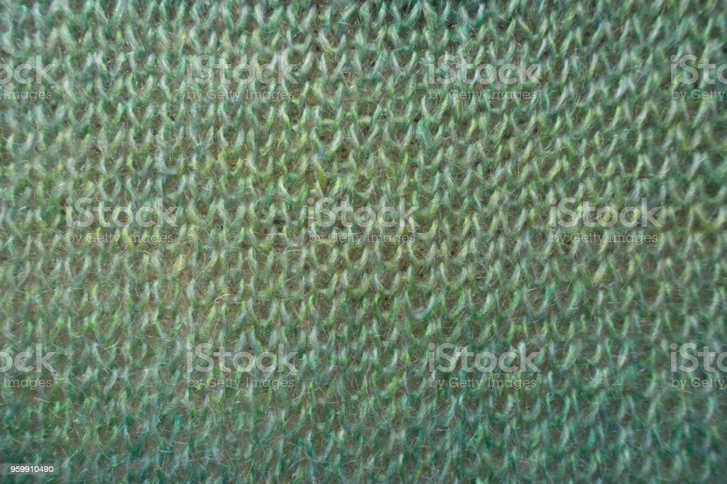 Closeup of green knitted fabric from above stock photo