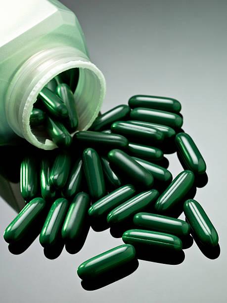 nahaufnahme der grünen details spilled aus der flasche - grüner tee kapseln stock-fotos und bilder