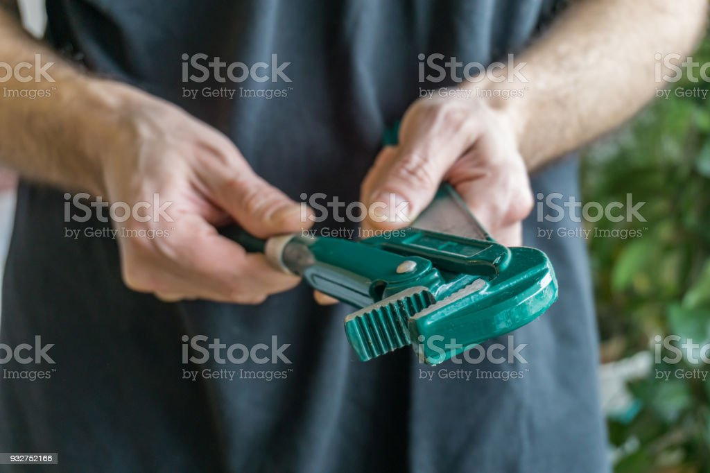Closeup of green plumbing wrench into the hands of a young man. stock photo