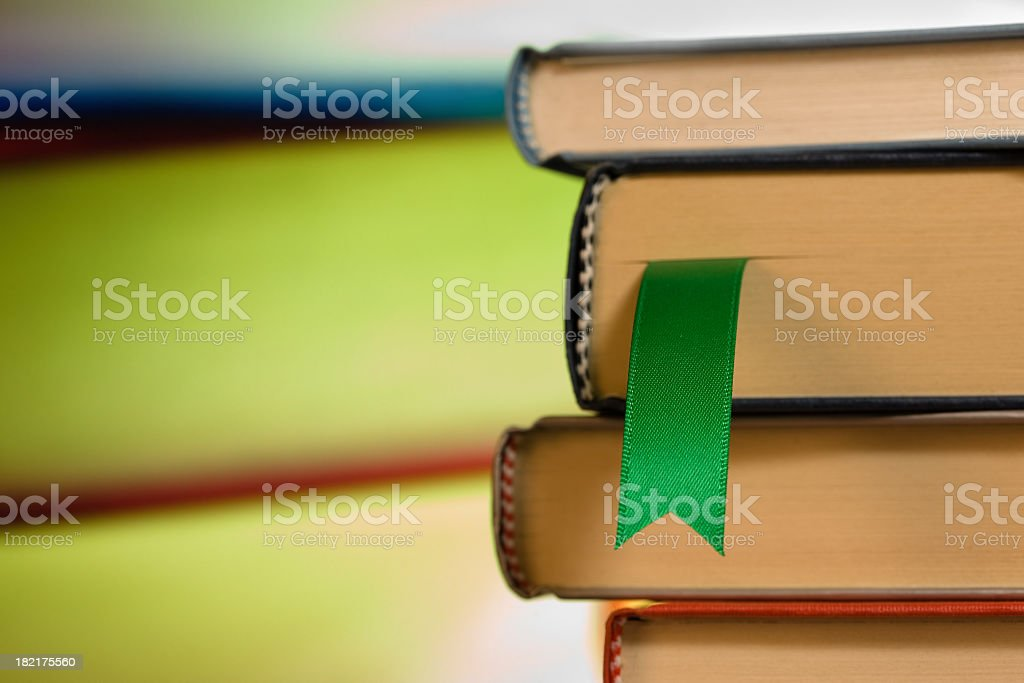 Close-up of green ribbon bookmark in a stack of books stock photo