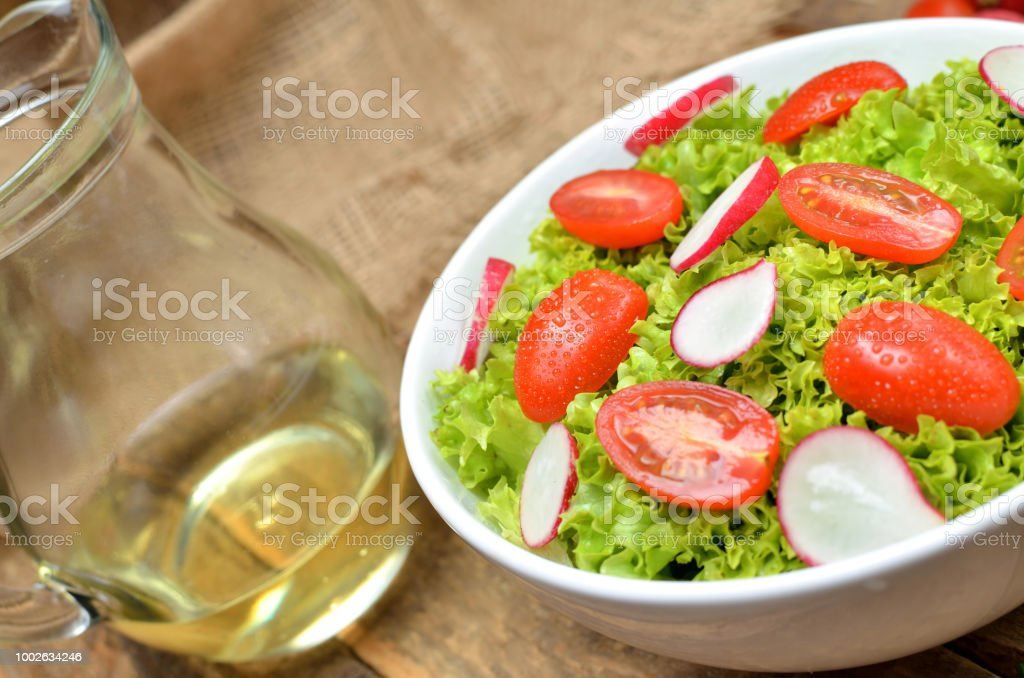 Close-up of green salad Lollo Biondo with tomatoes and radishes in a white bowl on wooden table and pitcher of oil stock photo
