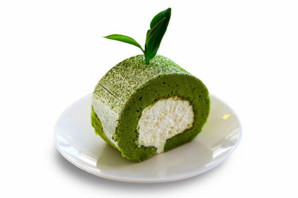 nahaufnahme von grüntee rollen kuchen mit weißen creme innen und grünem tee-blätter an der spitze, isoliert auf weißem hintergrund. lebensmittel oder dessert-snacks-konzept. - grüntee kuchen stock-fotos und bilder