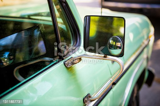 istock Closeup of green vintage retro style small car parked in Charleston, SC with reflection on side rear view mirror glass 1311857731