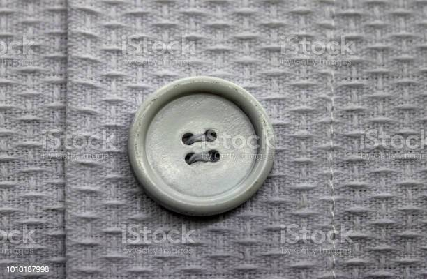 Closeup of greige button sewed on lighter twill fabric garment with picture id1010187998?b=1&k=6&m=1010187998&s=612x612&h=sjsot3trpjggcaw1c0nmq7ao iri36h42yle jh65co=