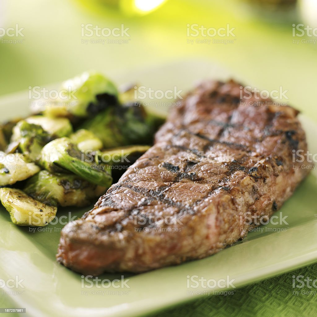 Close-up of grilled steak with side of Brussels sprouts stock photo