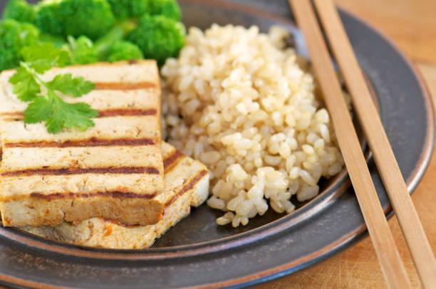 nahaufnahme von gegrillter tofu mit braunem reis - mariniertes tofu stock-fotos und bilder