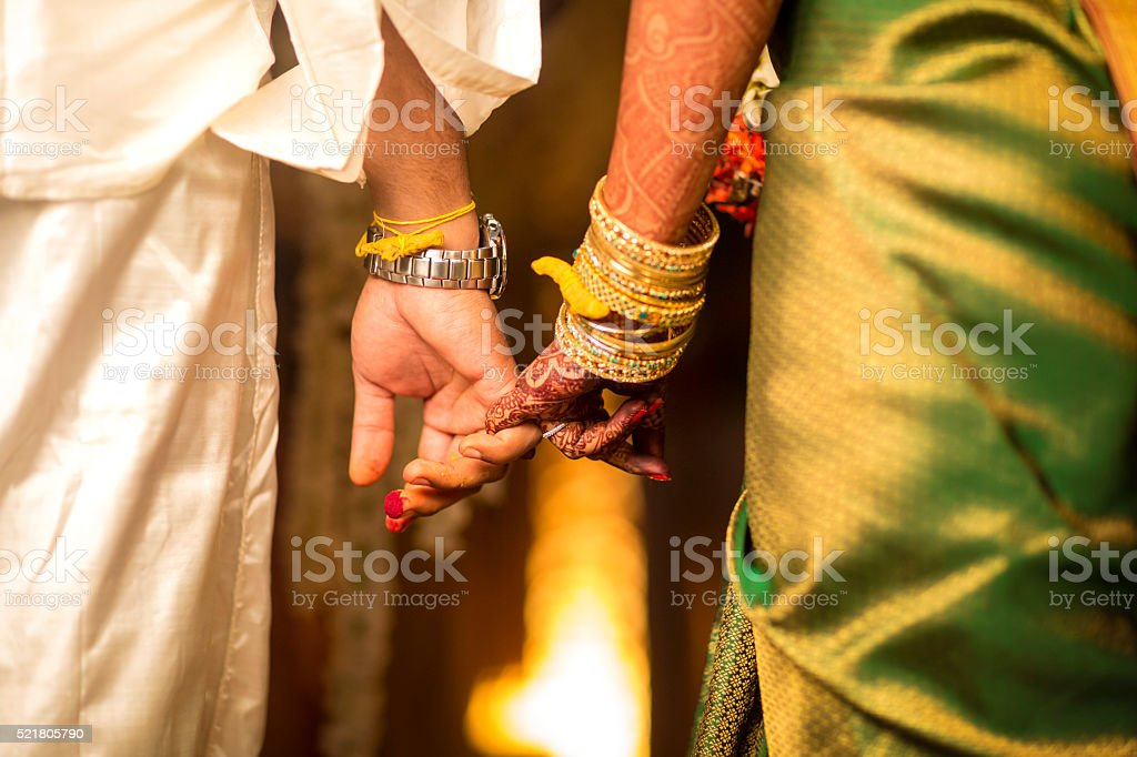 Close-up of groom holding brides hand stock photo