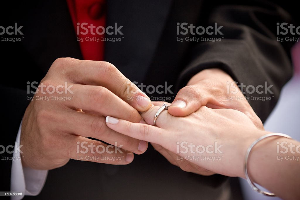 Close-up of groom placing a wedding ring on bride's finger royalty-free stock photo