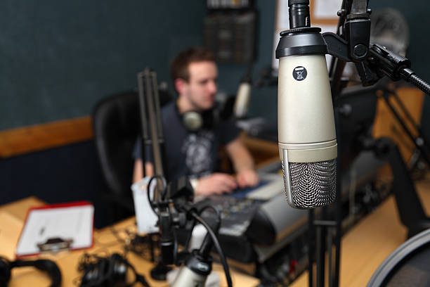 Close-up of guest microphone with blurred station background Guest view of Microphone in radio station - the radio presenter is broadcasting live in the background radio dj stock pictures, royalty-free photos & images