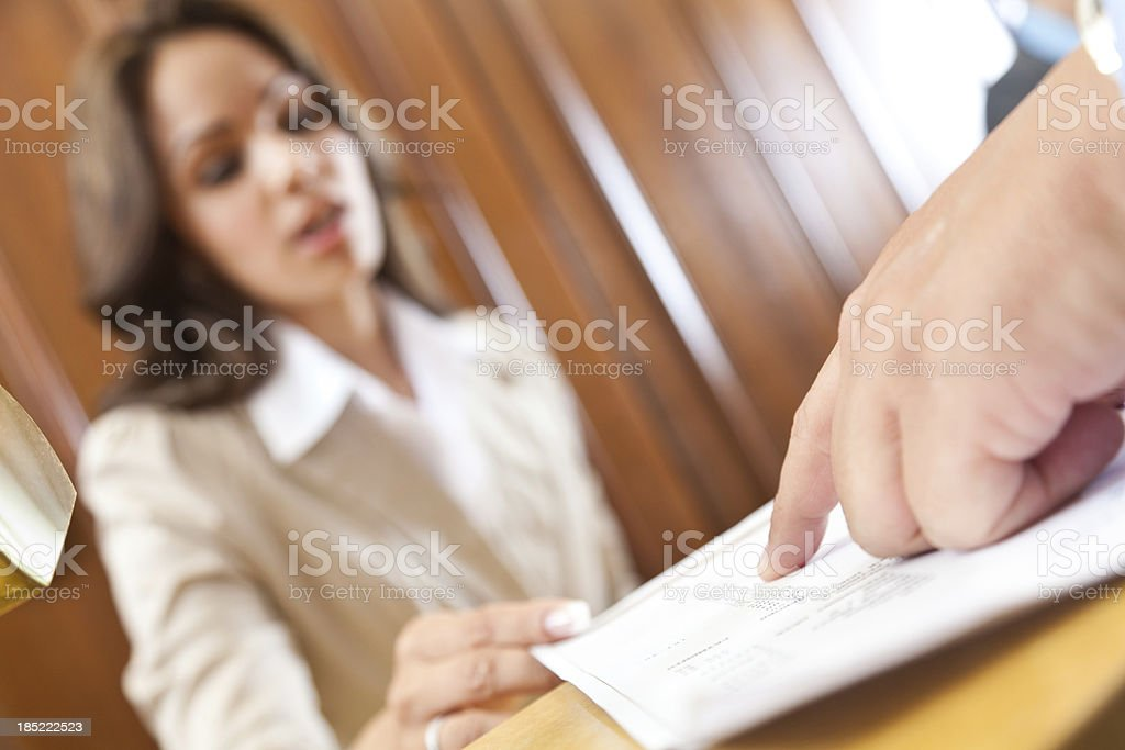 Closeup of guest pointing to hotel bill at front desk royalty-free stock photo